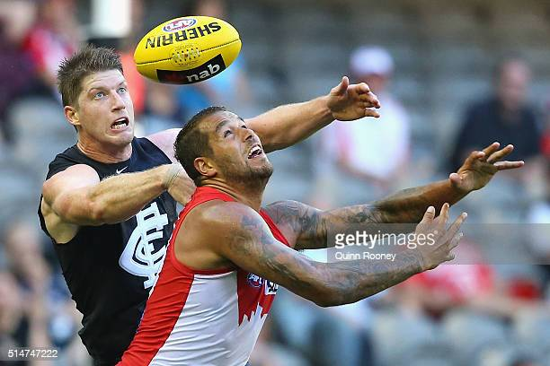 Sam Rowe of the Blues and Lance Franklin of the Swans compete for a mark during the NAB Challenge AFL match between the Carlton Blues and the Sydney...
