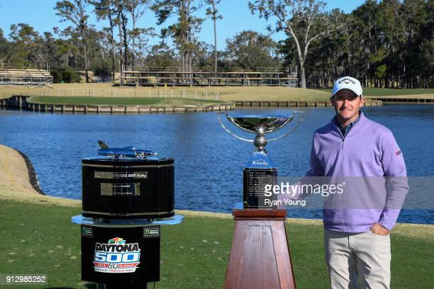 Sam Saunders poses with the Daytona 500 and FedEx Cup trophies on the 17th hole at THE PLAYERS Stadium Course at TPC Sawgrass on January 31 2018 in...