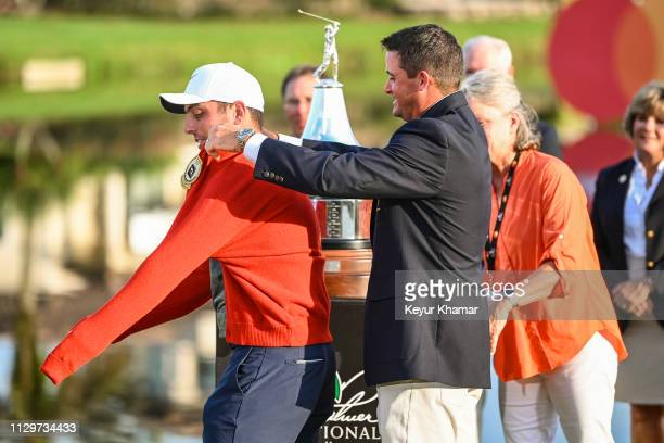 Sam Saunders puts a red cardigan on Francesco Molinari of Italy during the trophy ceremony following his two stroke victory in the final round of the...