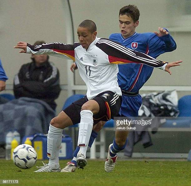Sam Sidney of Germany protects the ball from David Lesko of Slovakia during the men's under 18 international friendly match between Slovakia and...