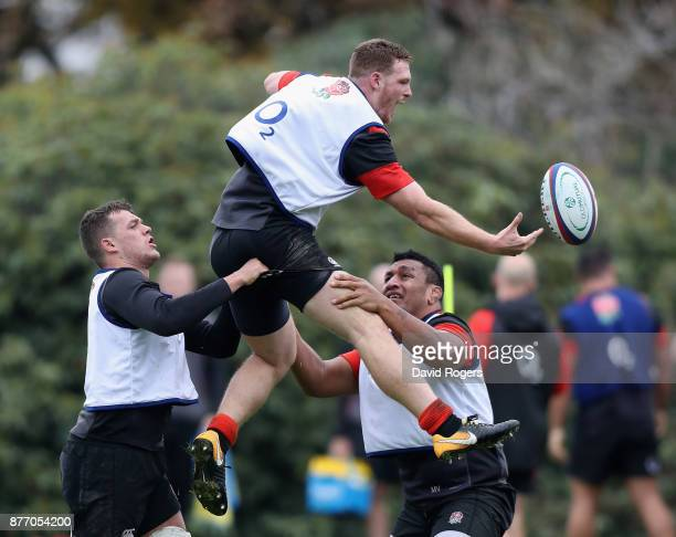 Sam Simmonds attempts to catch the ball as Zach Mercer and Mako Vunipola assist during the England training session held at Pennyhill Park on...