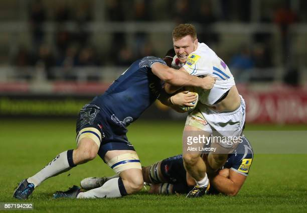 Sam Simmonds of Exeter Chiefs is tackled by Tom Curry and Jono Ross of Sale Sharks during the Aviva Premiership match between Sale Sharks and Exeter...