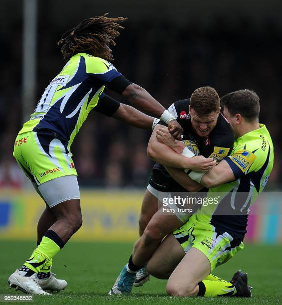 Sam Simmonds of Exeter Chiefs looks to break past Marland Yarde and Sam James of Sale Sharks during the Aviva Premiership match between Exeter Chiefs...