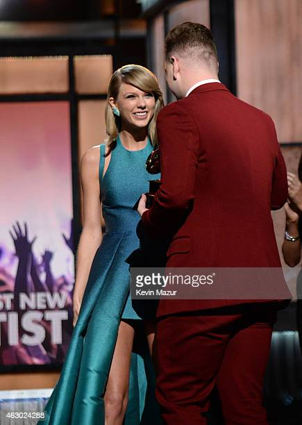 Sam Smith accepts award from Taylor Swift onstage during The 57th Annual GRAMMY Awards at the STAPLES Center on February 8 2015 in Los Angeles...