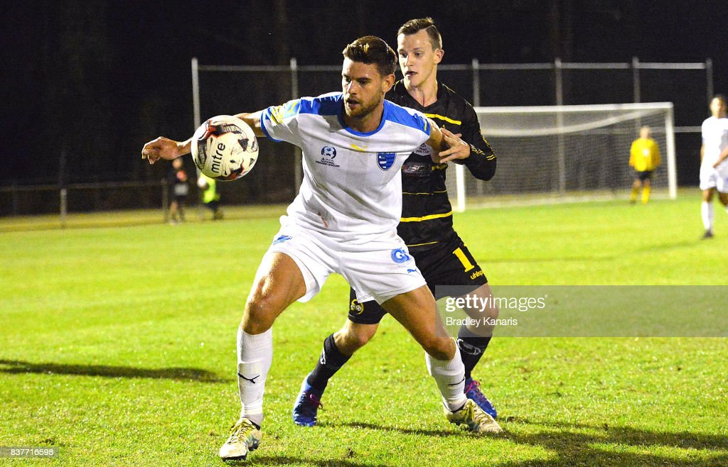 Sam Smith Gold Coast City is pressured by the defence of Stephen Green of Moreton Bay during the FFA Cup round of 16 match between Moreton Bay United and Gold Coast City at Wolter Park on August 23, 2017 in Brisbane, Australia.