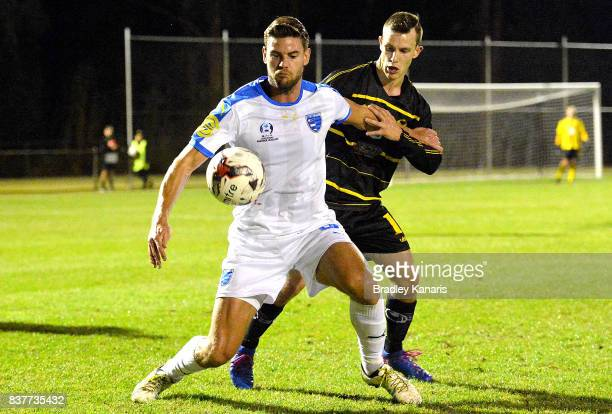 Sam Smith Gold Coast City is pressured by the defence of Stephen Green of Moreton Bay during the FFA Cup round of 16 match between Moreton Bay United...