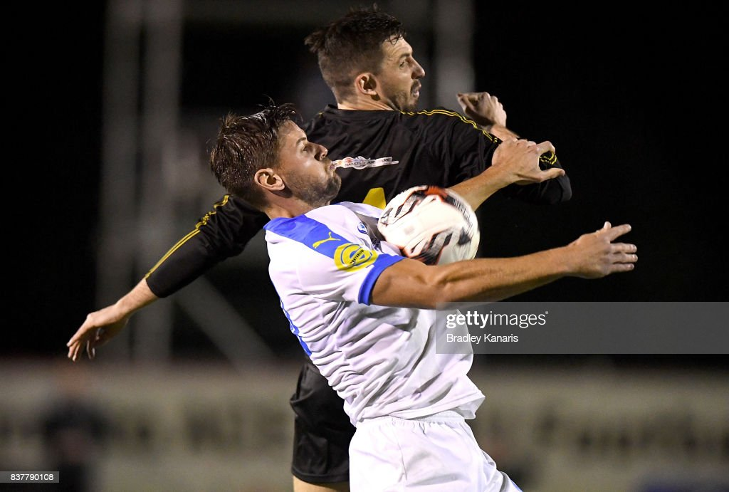 Sam Smith of Gold Coast City and Alex Janovsky of Moreton Bay challenge for the ball during the FFA Cup round of 16 match between Moreton Bay United and Gold Coast City at Wolter Park on August 23, 2017 in Brisbane, Australia.