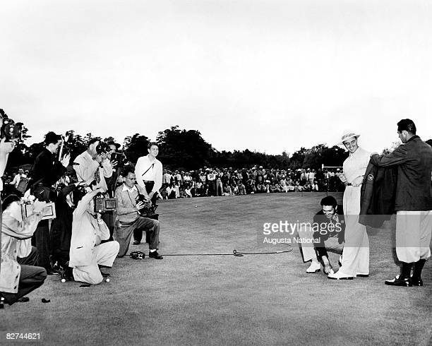 Sam Snead gets his first green jacket from Lloyd Mangrum as Johnny Bulla shines his shoes and a crowd of media photograph them during the...