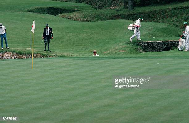 Sam Snead stands in Rae's Creek on the 13th hole of Amen Corner as Chi Chi Rodriguez his caddy and officials walk near the green during the 1974...