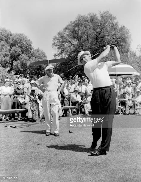 Sam Snead tees off as Byron Nelson watches during the 1953 Masters Tournament at Augusta National Golf Club in April 1953 in Augusta Georgia