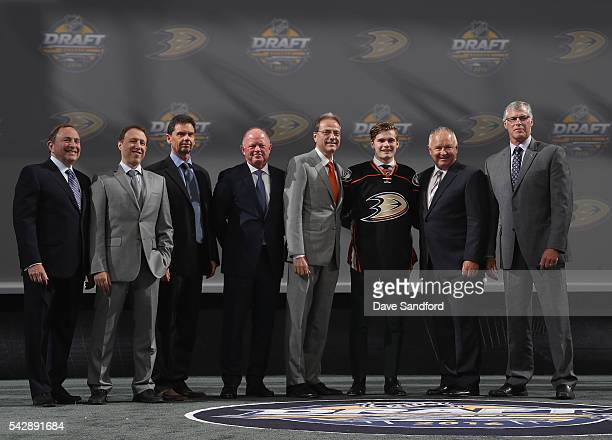 Sam Steel poses onstage with team personnel after being selected 30th overall by the Anaheim Ducks during round one of the 2016 NHL Draft at First...