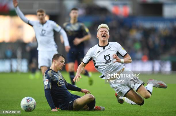 Sam Surridge of Swansea City is tackled by Mads Anderson of Barnsley during the Sky Bet Championship match between Swansea City and Barnsley at...