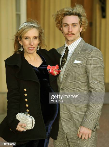 Sam TaylorWood wears her OBE with partner Aaron Johnson after it was presented to her by Prince Charles Prince of Wales during an Investiture...