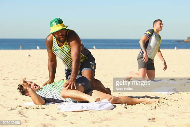 Sam Thaiday assists Cooper Cronk during stretching at the Australia Kangaroos Test team recovery session at Coogee Beach on May 2 2016 in Sydney...
