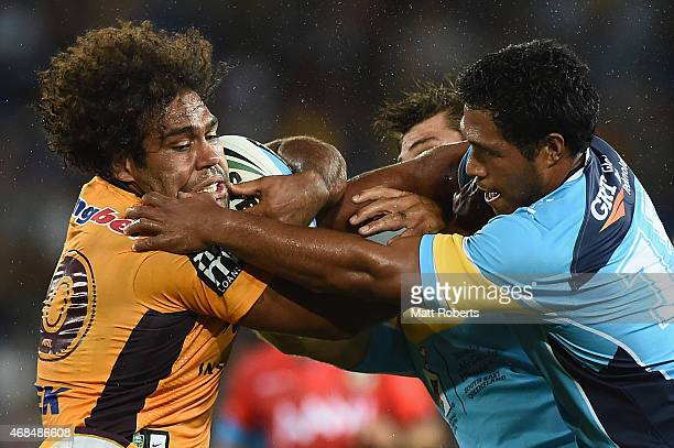 Sam Thaiday of the Broncos is tackled by Dave Taylor and Agnatius Paasi of the Titans during the round five NRL match between the Gold Coast Titans...