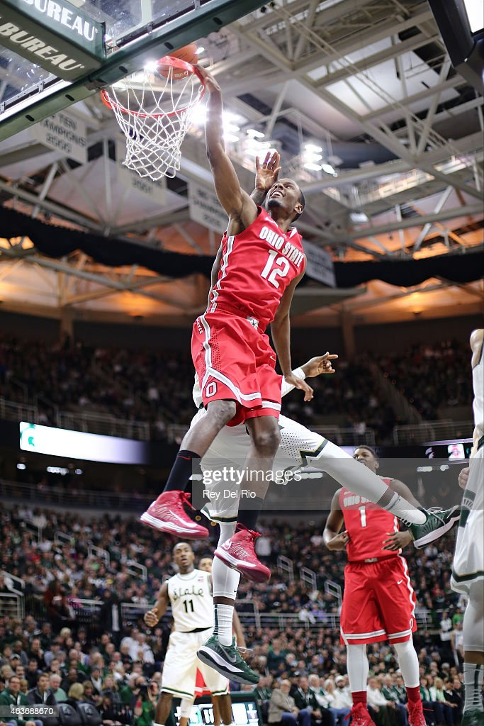 Sam Thompson #12 of the Ohio State Buckeyes drives to the basket and draws a foul from Branden Dawson #22 of the Michigan State Spartans at the Breslin Center on February 14, 2015 in East Lansing, Michigan.