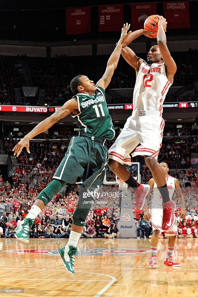Sam Thompson #12 of the Ohio State Buckeyes shoots over Keith Appling #11 of the Michigan State Spartans in the second half on February 24, 2013 at Value City Arena in Columbus, Ohio. Ohio State defeated Michigan State 68-60.