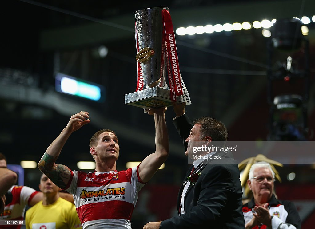 Sam Tomkins (L) and coach Shaun Wane (R) of Wigan Warriors lift the winners trophy after their 30-16 victory in the Super League Grand Final between Warrington Wolves and Wigan Warriors at Old Trafford on October 5, 2013 in Manchester, England.
