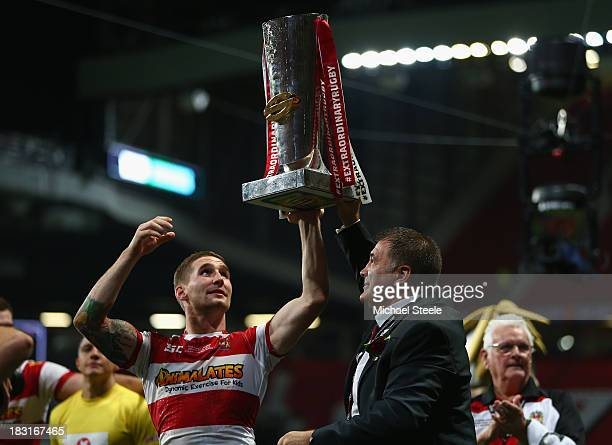 Sam Tomkins and coach Shaun Wane of Wigan Warriors lift the winners trophy after their 3016 victory in the Super League Grand Final between...