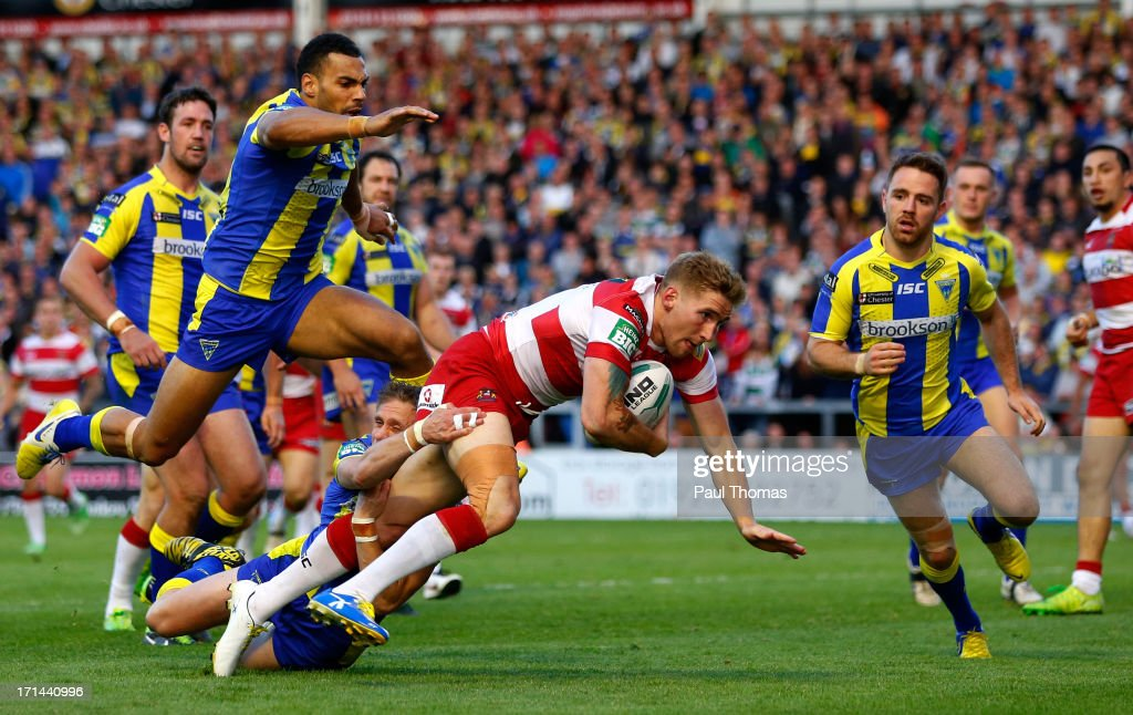 Sam Tomkins of Wigan dives over to score a try in the tackle of Warrington's Brett Hodgson during the Super League match between Warrington Wolves and Wigan Warriors at the Halliwell Jones Stadium on June 24, 2013 in Warrington, England.
