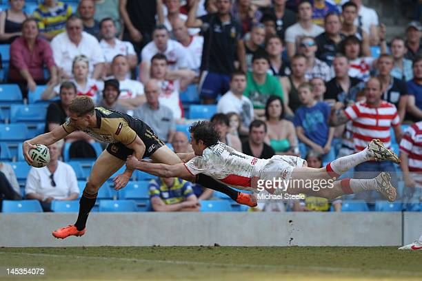 Sam Tomkins of Wigan Warriors scores a try as Paul Wellens of St Helens dives in vain during the Stobart Super League 'Magic Weekend' match between...