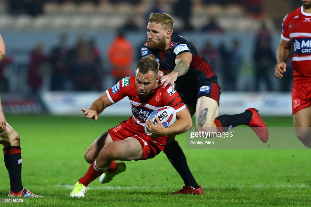 Sam Tomkins of Wigan Warriors tackles Adam Quinlan of Hull KR during the Betfred Super League at KCOM Craven Park on May 25, 2018 in Hull, England.