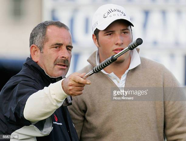 Sam Torrance of Scotland showws his son Daniel the line on the par four 17th hole during the first round of the Dunhill Links Championships on the...