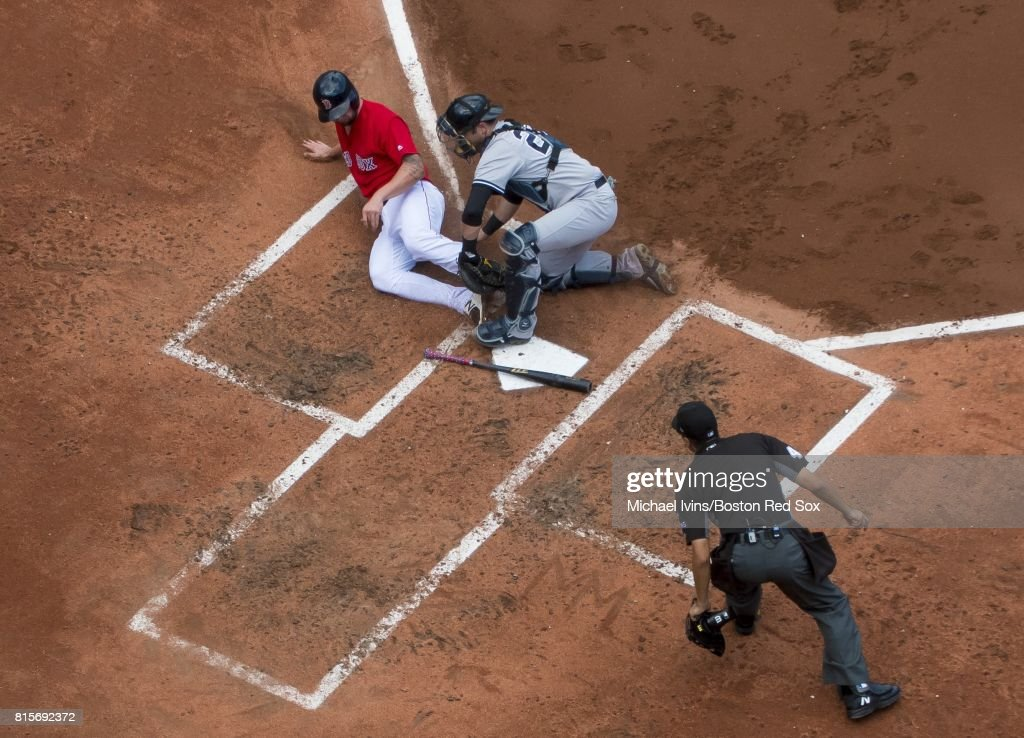 Sam Travis #59 of the Boston Red Sox is tagged out at the plate by Austin Romine #27 of the New York Yankees in the second inning during game one of a double header at Fenway Park on July 16, 2017 in Boston, Massachusetts.
