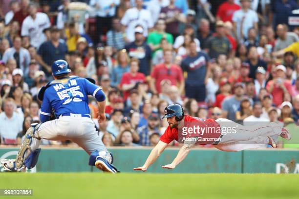 Sam Travis of the Boston Red Sox slides safely past the tag of Russell Martin of the Toronto Blue Jays in the second inning of a game at Fenway Park...