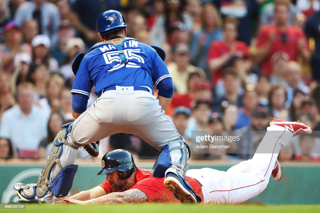 Sam Travis #59 of the Boston Red Sox slides safely past the tag of Russell Martin #55 of the Toronto Blue Jays in the second inning of a game at Fenway Park on July 13, 2018 in Boston, Massachusetts.