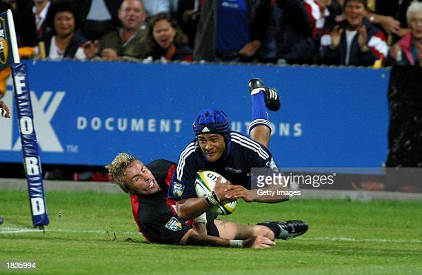 Sam Tuitupou of the Blues pushes off Justin Marshall of the Crusaders to score during the Super 12 match between the Auckland Blues and the...