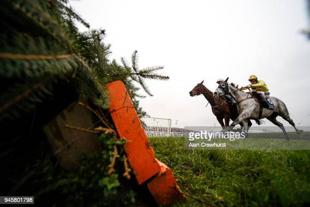 Sam TwistonDavies riding Politologue approach the last before winning The JLT Melling Chase from Min at Aintree racecourse on April 13 2018 in...