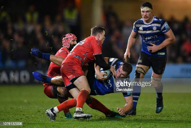 Sam Underhill of Bath is tackled by Chris Ashton and Josh Strauss of Sale Sharks during the Gallagher Premiership Rugby match between Bath Rugby and...