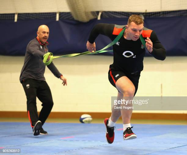Sam Underhill stretches as conditioning coach Dean Benton holds the restraining belt during the England conditioning session held at Nuffield Health...