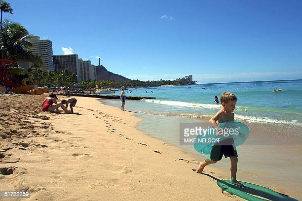 Sam Van Horne of San Diego California runs along Waikiki Beach in Hawaii 06 September 2001 near where sharks were sited 05 September afternoon which...