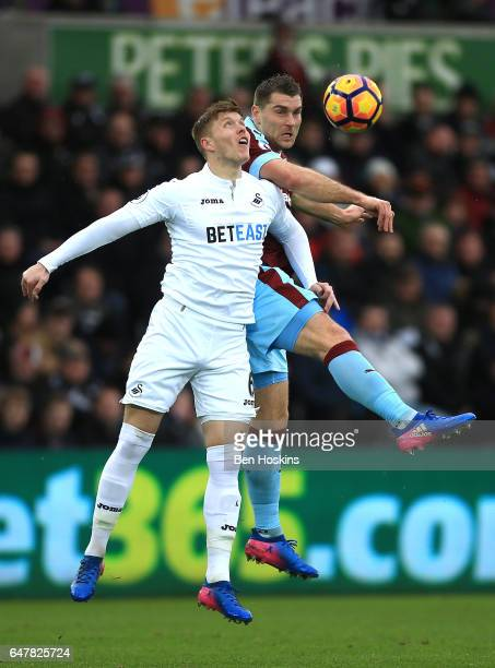 Sam Vokes of Burnley and Alfie Mawson of Swansea City battle to win a header during the Premier League match between Swansea City and Burnley at...