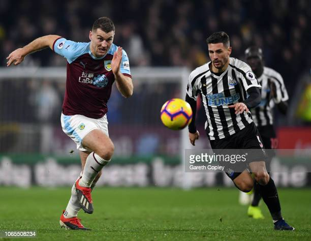 Sam Vokes of Burnley and Fabian Schar of Newcastle United chase the ball during the Premier League match between Burnley FC and Newcastle United at...