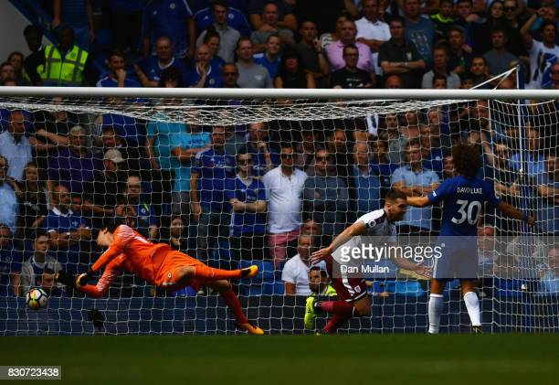 Sam Vokes of Burnley turns to celebrate after scoring his sides third goal past Thibaut Courtois of Chelsea during the Premier League match between...