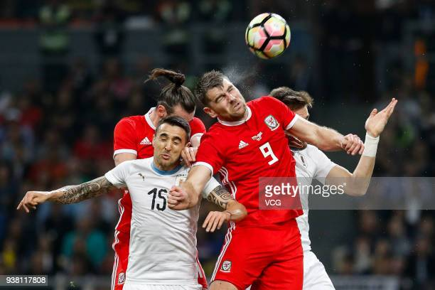 Sam Vokes of Wales and Matias Vecino of Uruguay compete for the ball during the 2018 China Cup International Football Championship match between...