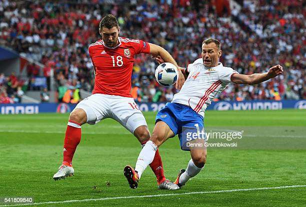 Sam Vokes of Wales and Vasili Berezutski of Russia compete for the ball during the UEFA EURO 2016 Group B match between Russia and Wales at Stadium...