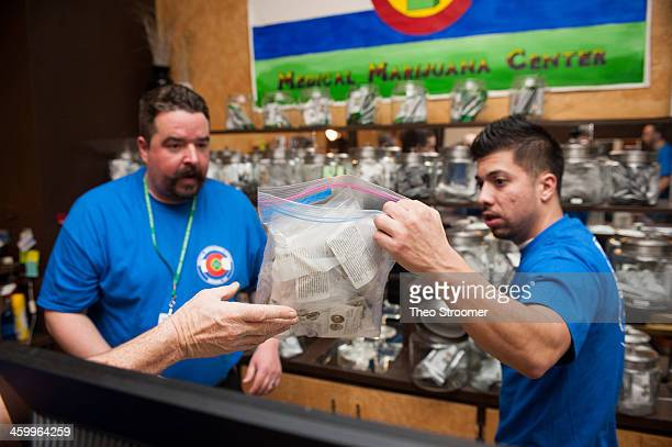 Sam Walsh left a budtender and facility manager David Martinez set up marijuana products as the 3D Denver Discrete Dispensary prepares to open for...