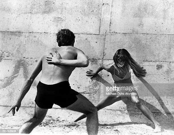 "Sam Waterston chases down Charlotte Rampling in a game of tag in a scene from the movie ""Three"" , circa 1967."