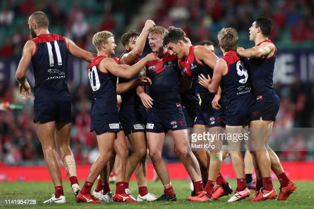 Sam Weideman of the Demons celebrates with team mates after kicking a goal during the round four AFL match between the Sydney Swans and the Melbourne...