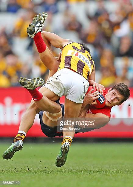 Sam Weideman of the Demons is hit in a big tackle by Cyril Rioli of the Hawks during the round 20 AFL match between the Melbourne Demons and the...