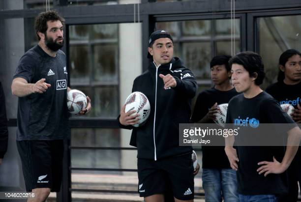 Sam Whitelock and Anton Lienert Brown of New Zealand All Blacks give instructions to the children give directions to the children during a sports...