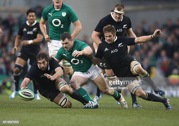 Sam Whitelock of the All Blacks races Cian Healy and team mate Richie McCaw to the loose ball during the International match between Ireland and New...
