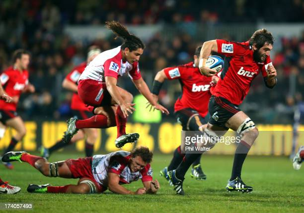 Sam Whitelock of the Crusaders breaks the tackle of Saia Faingaa and Jake Schatz of the Reds during the Super Rugby Qualifying Final match between...