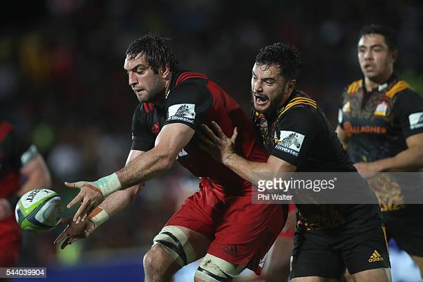 Sam Whitelock of the Crusaders is tackled by James Lowe of the Chiefs during the round 15 Super Rugby match between the Chiefs and the Crusaders at...