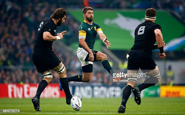 Sam Whitelock of the New Zealand All Blacks kicks past Willie Le Roux of South Africa during the 2015 Rugby World Cup Semi Final match between South...