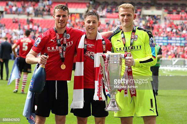 Sam Winnall Josh Brownhill and Adam Davies of Barnsley with the trophy as he celebrates promotion after winning the Sky Bet League One Play Off Final...